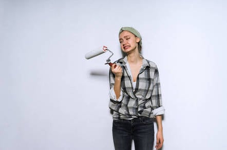 A woman cries while holding a paint roller