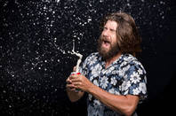 beardy chap pulls beer tab and it sprays in his face
