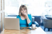 woman clicks the wrong thing on laptop, covers mouth from shock