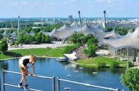 A boy plays on some railing on a hill overlooking Munich's Olympic grounds. - where the stadium will be built.