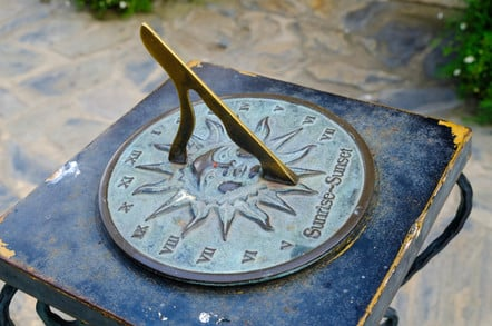 Close-up of a brass sundial mounted on a stone plinth in a garden
