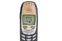 someone attempting to use SMS on a Nokia 6310i cellphone.