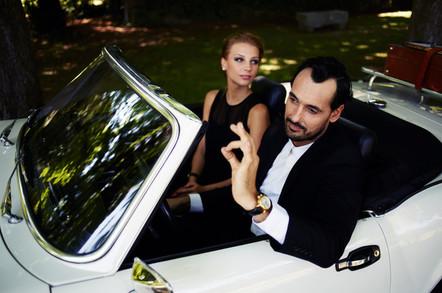 Wealthy couple sitting inside luxury car