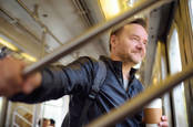 man smiles wryly during journey on bus