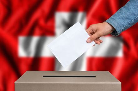 Woman's hand casting ballot in front of Swiss flag