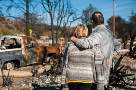 A couple stare at their wrecked home