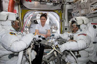 NASA astronaut Christina Koch (center) assists fellow astronauts Nick Hague (left) and Anne McClain