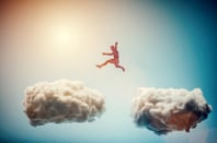 Man jumping from one cloud to another