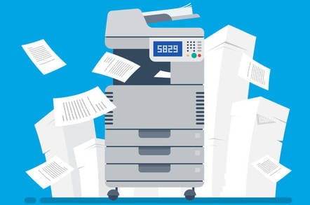 A printer with stacks of paper next to it