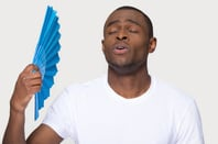 Guy cooling himself down with fan