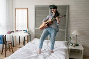 Woman sings, plays guitar while wearing VR headset