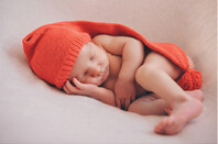Newborn baby sleeps in woolly hat