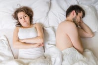 oung man is sleeping in bed. Sad, disappointed and unsatisfied girlfriend lying near