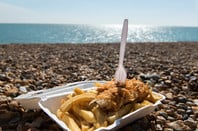 fish and chips takeaway container on beach