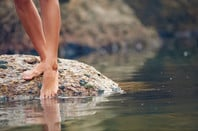 Woman on rock at beach dipping toes in water