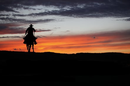 Cowboy silhouette on a horse during sunset