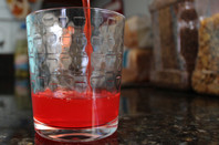 Pouring red drink into glass