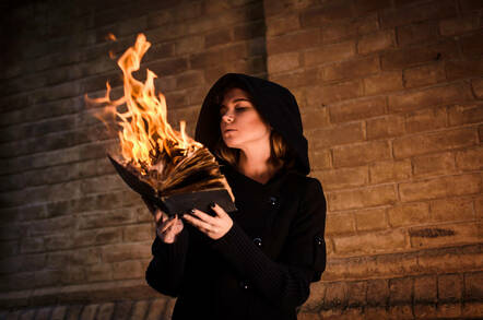 A person holding a burning book