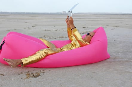 man in gold suit on beach lies on gold pillow