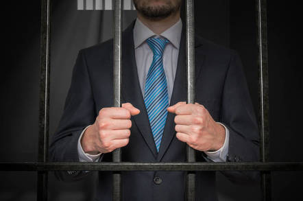 Someone behind bars in a suit
