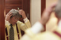 man tries on fake-looking toupee