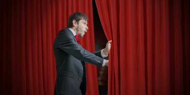 Curious actor or illusionist is looking behind red curtain