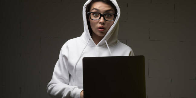 Someone in a white hoodie holding a laptop
