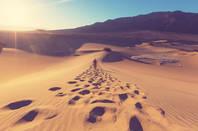 Someone walking on big sand dunes