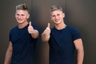 twin men give the thumbs up