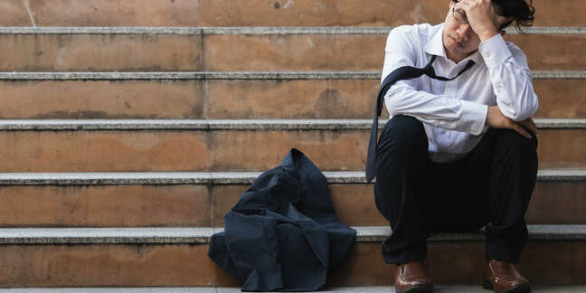 worker sits on steps after being told about redundancy