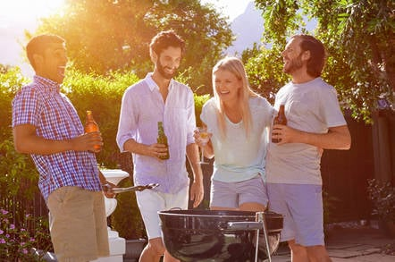 A group of people around a BBQ grill