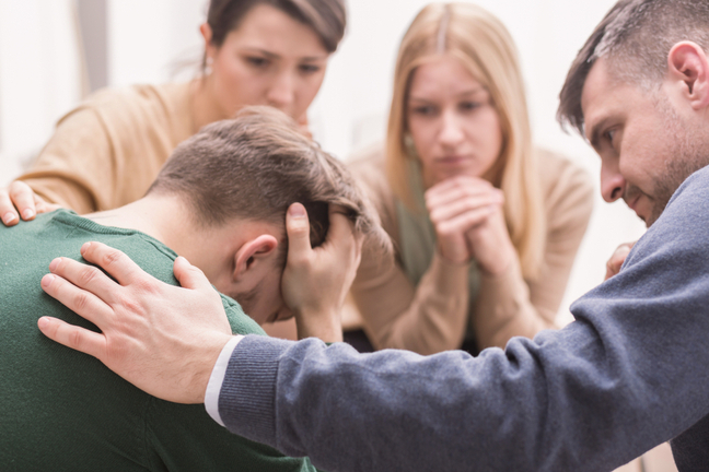 Devastated young man and friends supporting him during group therapy