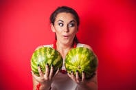 Image of a woman holding a pair of watermelons