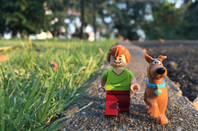 scooby doo and shaggy do figurines stroll across pavement