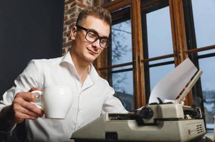 man with old-fashioned typewriter in office