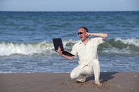 sunburned man shouts down phone while on laptop on the beach