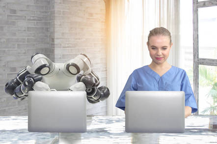 A robot and a human typing next to each other