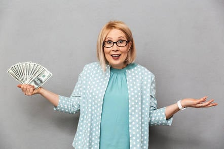 A woman shrugging with a pile of cash