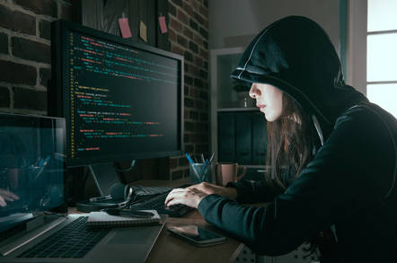 "A woman in the classic ""black hoodie hacker"" shot"