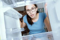 Shocked woman looking into fridge