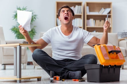 Man not enjoying assembling furniture at home