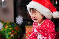 little girl cries in christmas hat