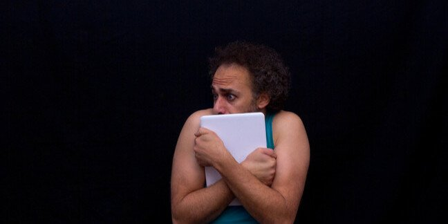Man holding a laptop and looking scared