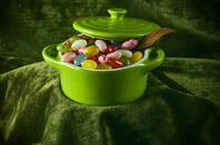 jelly beans in an earthenware pot against a green velvet draped background