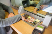 A person receiving cash from a teller