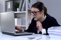 Someone chewing nervously on a pencil at work in front of a laptop