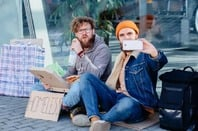 Two homeless men with a phone