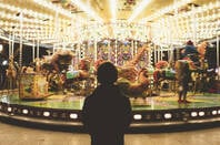 A kid standing in front of a merry-go-round