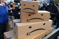 Boxes with Amazon's smile logo upside down to form frowns