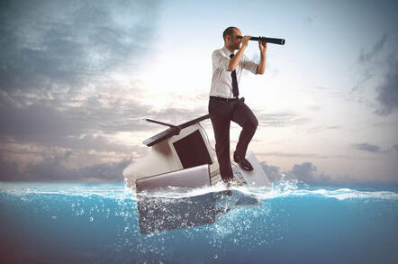 A guy adrift in an ocean on a laptop and monitor